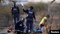 Tim medis dibantu oleh polisi Afrika Selatan menolong seorang pekerja tambang yang tertembak di Rustenburg, Kamis (16/8). 34 orang pekerja tambang tewas akibat tembakan polisi Afsel.