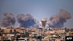 El humo se eleva por encima de las zonas controladas por los rebeldes de la ciudad de Daraa durante los ataques aéreos informados por las fuerzas del régimen sirio, el 5 de julio, 2018.