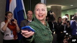 In this Dec. 8, 2011, file-pool photo, then-Secretary of State Hillary Clinton hands off her mobile phone after arriving for a meeting in The Hague, Netherlands. (AP Photo/J. Scott Applewhite, FILE)