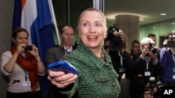 FILE - In this Dec. 8, 2011, file-pool photo, then-Secretary of State Hillary Rodham Clinton hands off her mobile phone after arriving for a meeting in The Hague, Netherlands.