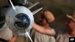 러시아 군인들이 시리아 공군기지에서 전투기에 장착된 미사일 점검을 하고 있는 시리아 요원들을 돕고 있다.