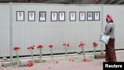 سینٹ پیٹرزبرگ میں ایک خاتون اس عارضی یادگار کے پاس کھڑی ہے جہاں کرونا وائرس کے مریضوں کا علاج کرتے ہوئے ہلاک ہوجانے والے طبی کارکنوں کی تصویریں لگی ہیں