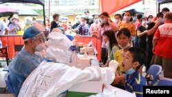 A medical worker collects a swab from a resident during a mass testing for the coronavirus disease (COVID-19) at a makeshift testing site at a stadium in Guangzhou, Guangdong province, China May 30, 2021.
