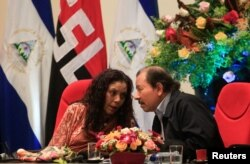 FILE - Nicaraguan President Daniel Ortega speaks with his wife and vice president, Rosario Murillo, during an event to commemorate the 38th anniversary of the founding of the Nicaraguan army, in Managua, Sept. 1, 2017.