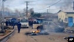 La police de prend le contrôle d'une rue bloquée par une barricade en feu, dans le quartier Cocotiers de Libreville, au Gabon, 15 août 2012 (Archives). (AP Photo / Joel Bouopda Tatou)