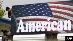 Công nhân Trung Quốc treo bảng hiệu cho một cửa hàng bán xe môtô của Mỹ ở Bắc Kinh, ngày 16/4/2011