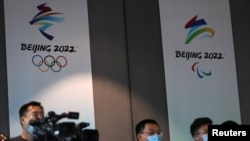 Reporters are seen in front of the Beijing 2022 Winter Olympic and Paralympic Games signs during a news conference on the construction progress of the sports event venues, at the headquarters of the Beijing Organising Committee, in Beijing, China July 30…