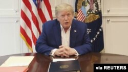 U.S. President Donald Trump, who is being treated for COVID-19 in a military hospital outside Washington, speaks from his hospital room, in this still image taken from a video supplied by the White House, Oct. 3, 2020.