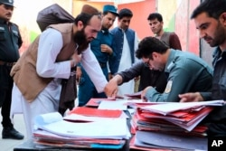 Taliban prisoners are checked with documents as they are released from Pul-e-Charkhi jail in Kabul, Afghanistan, Aug. 13, 2020, in this picture provided by Afghanistan's National Security Council.