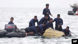 Indonesian Navy divers pull out a part of an airplane out of the water during a search operation for the Sriwijaya Air passenger jet that crashed into the sea near Jakarta, Indonesia, Jan. 10, 2021.