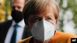 German Chancellor Angela Merkel arrives about a news conference German Government's corona policy in Berlin, Germany, Monday, Nov. 2, 2020. (AP Photo/Markus Schreiber)