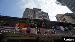 People look out from a common balcony of a Chawl, home to hundreds of families, during a 21-day nationwide lockdown to slow the spreading of coronavirus disease (COVID-19), in Mumbai, India, March 31, 2020.