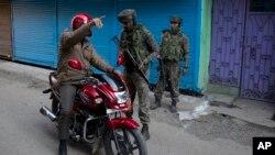 سری نگر میں بھارتی فوجی ایک کشمیری راہگیر سے پوچھ گچھ رہے ہیں۔