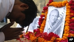 A student pays tribute to legendary Indian sitar player Ravi Shankar at the Bengali Tola Inter College, where Shankar had studied in Varanasi, India, Dec. 12, 2012.