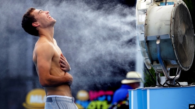 Poland's Jerry Janowicz is sprayed with cool water at the Australian Open tennis championship in Melbourne, Australia, Thursday, Jan. 16, 2014.