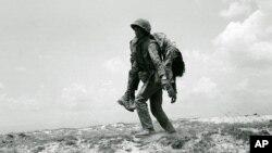 Một binh sĩ Thủy quân lục chiến miền Nam Việt Nam mang thi thể đồng đội tử trận đi trên Quốc Lộ 1, tỉnh Quảng Trị, ngày 30/4/1972. Hiện có khoảng nửa triệu người Việt thiệt mạng trong chiến tranh mà chưa được xác định.