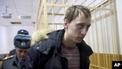 Pavel Dmitrichenko, foreground, is escorted out of a courtroom in Moscow, March 7, 2013.