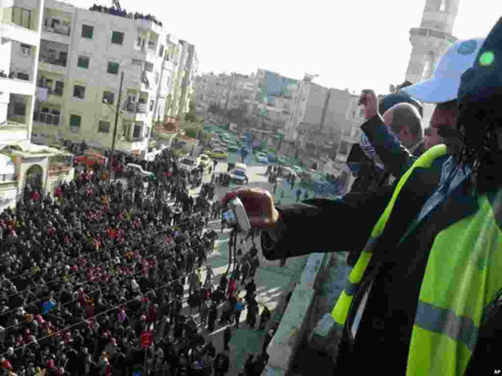 Arab League observers take photos of anti-government protesters on the streets in Adlb, Syria on December 30, 2011. (Reuters)
