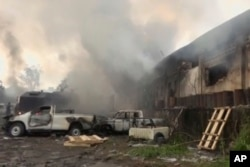 In this image from video, smoke envelopes a building as emergency services attend an early-morning fire in Congo's capital Kinshasa, Dec. 13, 2018, which is reported to have destroyed thousands of voting machines just 10 days before the upcoming presidential election.