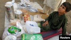 Adnan, 8, whose family fled from the military offensive against Pakistani militants in North Waziristan, sells ration packs that were collected by his family from a distribution point for internally displaced persons in Bannu,Khyber-Pakhtunkhwa province,