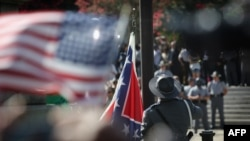 A South Carolina state police honor guard lowers the Confederate flag from the Statehouse grounds in Columbia, July 10, 2015.