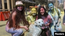 "FILE - People pose with a dog covered in colour powder during the first color run called ""Alwan LB"" in Beirut May 3, 2015. (REUTERS/Mohamed Azakir)"