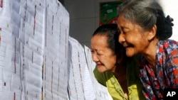 Người dân xem danh sách tên các ứng cử viên quốc hội tại 1 trạm bỏ phiếu ở Bali, Indonesia, 9/4/2014