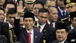 印尼總統佐科威星期一﹐在議會大廈舉行的就職儀式上與副總統在一起,向人們招手示意。