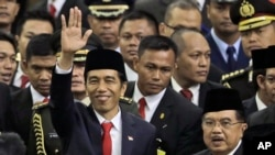 印尼总统佐科威星期一在议会大厦举行的就职仪式上与副总统在一起,向人们招手示意。
