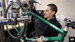 """Rose Barcklow sedang membetulkan sepedanya di """"ruang velo,"""" semacam bengkel kecil khusus untuk sepeda, di dalam kompleks apartemennya di Denver, Colorado (foto: dok)."""