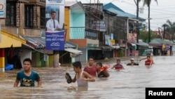 Warga mengarungi banjir yang dibawa hujan monsoon dan diperburuk oleh badai tropis Trami, di Cavite, bagian selatan Manila (19/8). (Reuters/Romeo Ranoco)