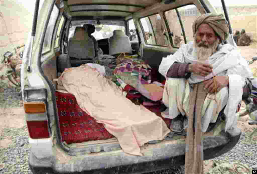 An elderly Afghan man sits next to the covered body of a person who was allegedly killed by a U.S. service member, in a minibus in Panjwai, Kandahar province south of Kabul, Afghanistan, Sunday, March 11, 2012. A U.S. service member walked out of a base i