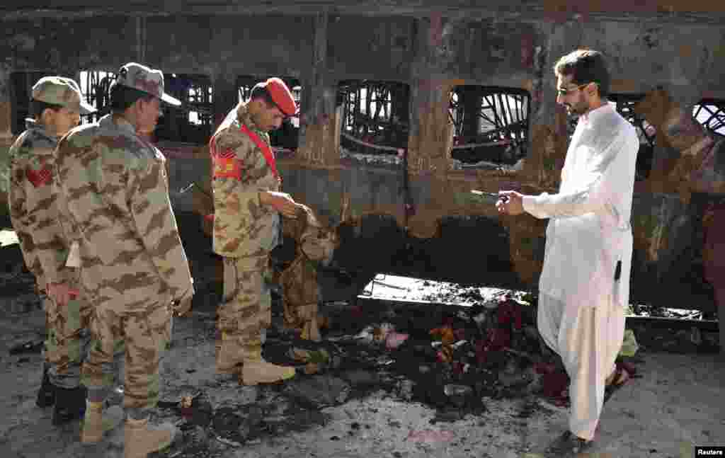 Security officials collect evidence near a damaged passenger carriage at the site of a bomb blast in the town of Sibi, Pakistan, April 8, 2014.