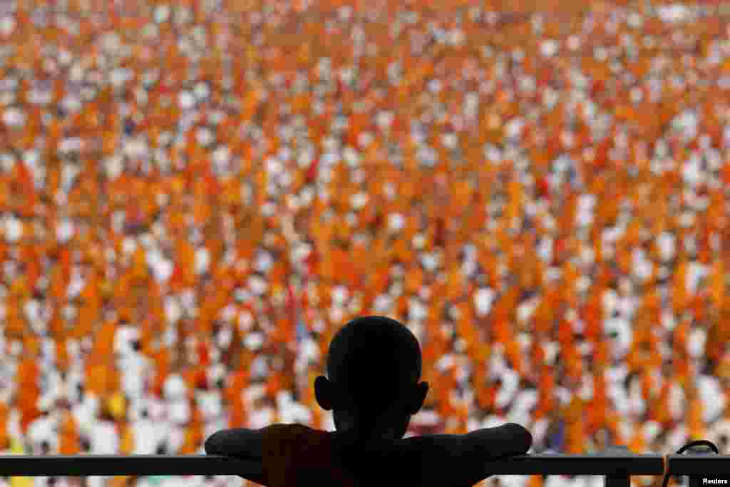 Buddhist monks and novices gather to receive alms at Wat Phra Dhammakaya temple, in what organizers said was a meeting of over 100,000 monks, in Pathum Thani, outside Bangkok, Thailand.
