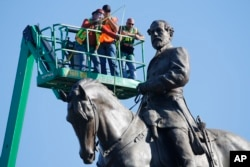 An inspection crew from Virginia takes measurements as they inspect the statue of Confederate Gen. Robert E. Lee June 8, 2020, in Richmond, Va. Virginia Gov. Ralph Northam has ordered the removal of the statue. (AP Photo/Steve Helber)