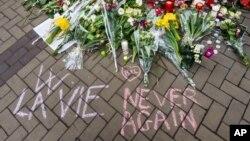 """Un homme écrit """"la vie, never again"""" avec de la craie près de la station de métro de Maelbeek, Bruxelles, 24 mars 2016."""