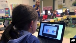 FILE - Fifth grader Ashlynn De Filippis, left, solves math problems on the DreamBox system as teacher Heather Dalton, center rear, works with other students in class at Charles Barnum Elementary School in Groton, Connecticut, Sept. 20, 2018.