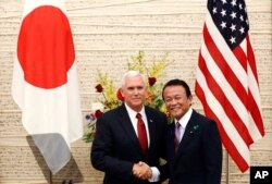 FILE - U.S. Vice President Mike Pence, left, and Japanese Deputy Prime Minister and Finance Minister Taro Aso pose for a photo at the end of their joint press conference at the prime minister's office in Tokyo, April 18, 2017.