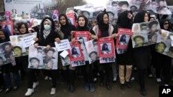 妇女们在喀布尔举着被塔利班杀害的民族哈扎拉人的头像(2015年11月11日)。