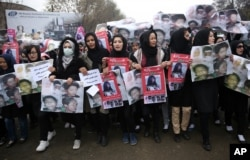 FILE - Women march in the Afghan capital of Kabul on Wednesday, Nov. 11, 2015 with pictures showing ethnic Hazaras who were allegedly killed by the Taliban, calling for a new government that can ensure security in the country.