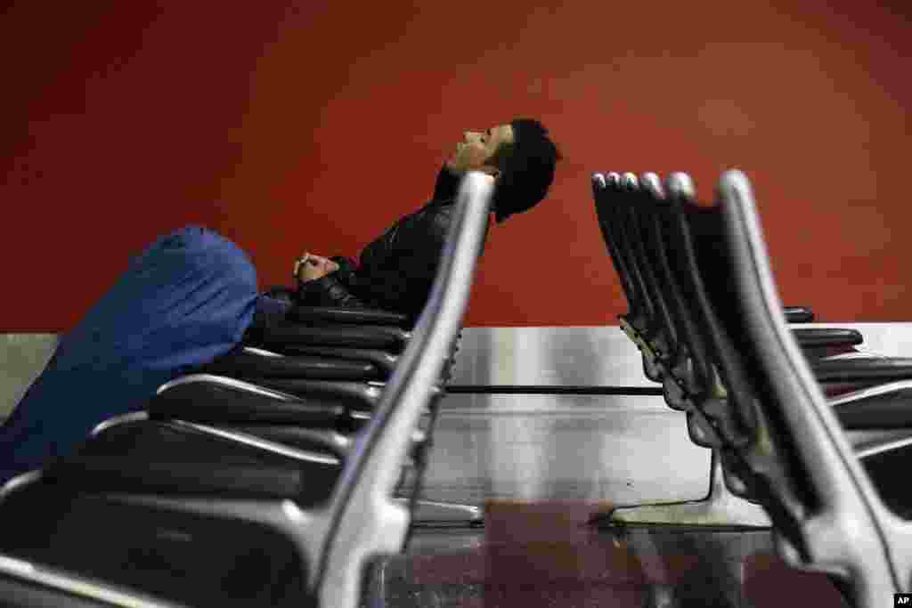 A man sleeps at the Los Angeles International Airport in Los Angeles. More than 43 million people are to travel over the long Thanksgiving holiday weekend, according to AAA (American Automobile Association).