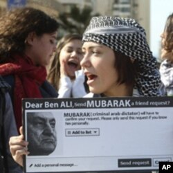 A protester carries a sign referring to ousted Tunisian President Zine al-Abidine Ben Ali and Egypt's President Hosni Mubarak during a demonstration against Mubarak in front of the Egyptian Embassy in Beirut, Feb 5, 2011