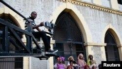 """Un cameraman filme une scène à partir d'une grue au cours du tournage de """"Ake,"""" un film basé sur les mémoires d'enfance de l'écrivain nigérian Wole Soyinka, à Abeokuta, au sud-ouest du Nigeria, 14 juillet 2013."""