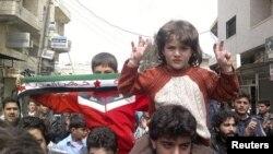 ບັນດາພວກປະທ້ວງຕໍ່ຕ້ານປະທານາທິບໍດີຊີເຣຍ ທ່ານ Bashar al-Assad ທີ່ Kafranbel ໃກ້ໆເມືອງ Idlib ທີ 1 ເມສາ, 2012.