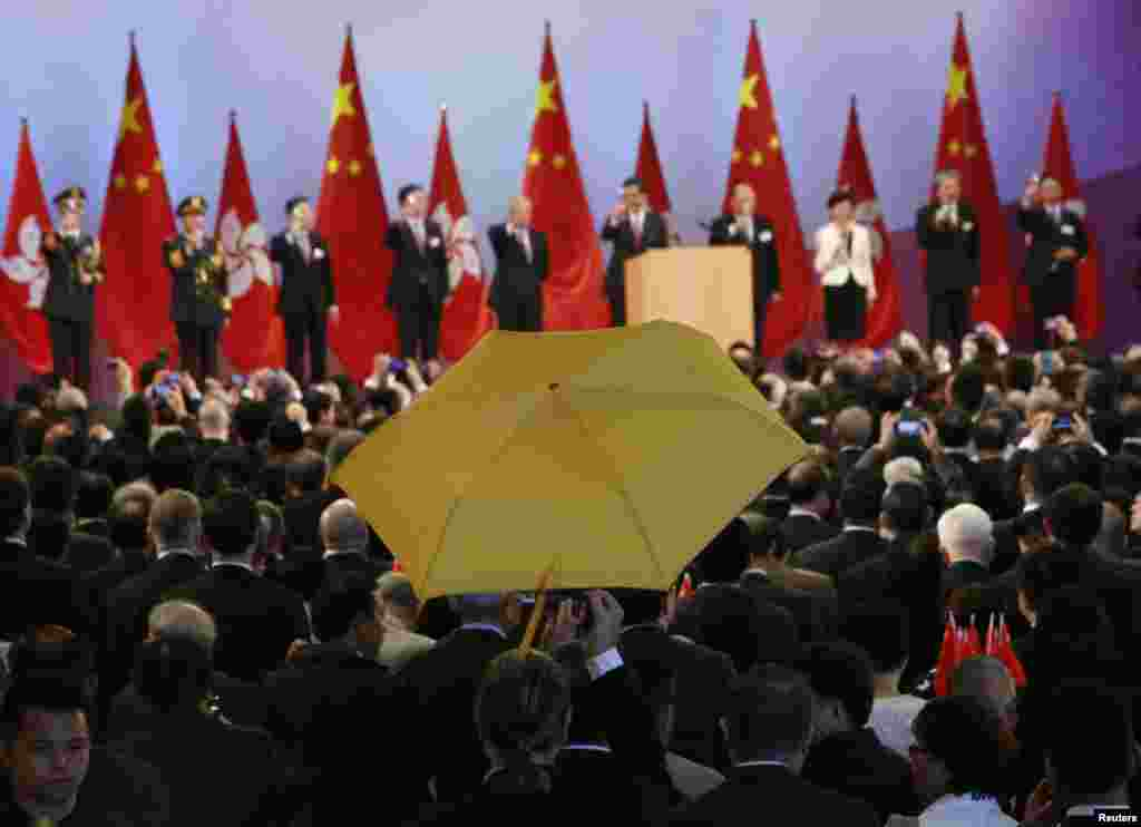 Paul Zimmerman, a district councilor, raises a yellow umbrella as Hong Kong Chief Executive Leung Chun-ying (5th R) and other officials make a toast to guests at a reception following a flag-raising ceremony in Hong Kong, celebrating the 65th anniversary of China National Day.