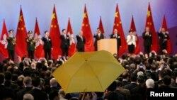 Ông Paul Zimmerman, hội viện hội đồng quận, giơ cao chiếc ô (dù) vàng khi trưởng Đặc khu Hành chính Lương Chấn Anh (thứ 5 bên phải) cùng các quan chức khác nâng rượu mừng tại một buổi tiếp đón sau lễ kéo cờ nhân ngày Quốc khánh Trung Quốc, 1/10/2014.