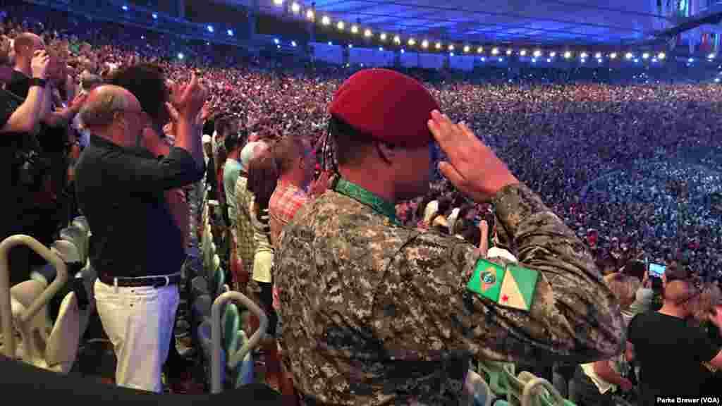 Un militaire salue l'hymne national du Brésil qui est joué au début de la cérémonie d'ouverture des Jeux Olympiques d'été de 2016 dans le Stade Maracaña, à Rio de Janeiro, Brésil , 5 août 2016.
