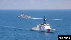 """美国海军公布的图片显示美国海军""""基德""""号阿利·伯克级导弹驱逐舰与美国海岸警卫队""""蒙罗""""号传奇级巡逻舰在当地时间2021年8月27日例行穿越台湾海峡的国际水域。"""