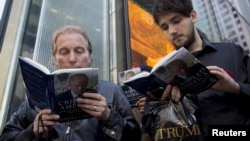 "FILE - People read as they wait in line for Republican presidential candidate Donald Trump to sign copies of his new book ""Crippled America"" in the Manhattan borough of New York, Nov. 3, 2015."