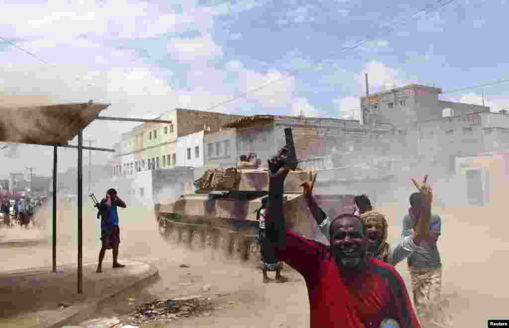 Southern Popular Resistance fighters react as one of their tanks fire at a Houthi position during fighting in Yemen's southern city of Aden.